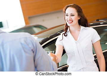 Woman shaking hands with car salesman, buying a new car