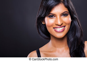 happy young indian woman against black background