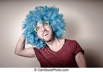 hipster stylish funny man with blue wig on gray background