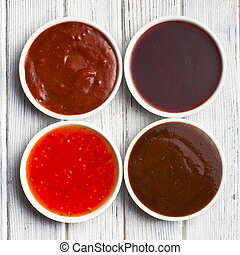 various barbecue sauces in ceramic bowls - the various...