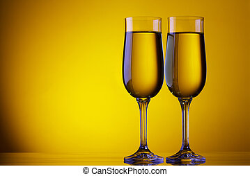Two champagne flute glasses on yellow background with copy...