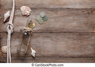 Weathered wooden table with rope, shells, message bottle and vintage coins