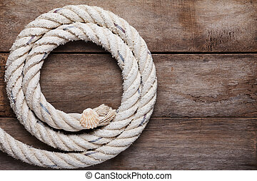 Sea rope with shell on wooden background