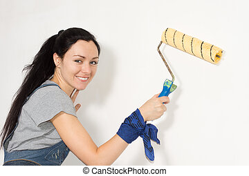 Smiling woman painting her house