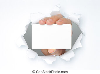 Hand holds white card through white torn paper