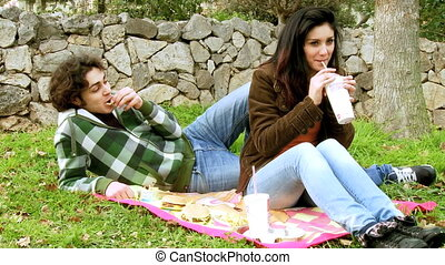 Eating junk food in park - Happy couple eating hamburger and...