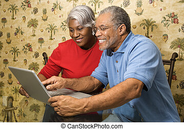 Mature couple with laptop. - Portrait of mature African...