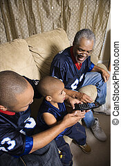 Family watching sports. - Three male generations of an...