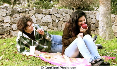 Young couple eating junk food - Woman eating healthy food...