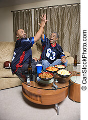 Men watching sports - African-American father and son giving...