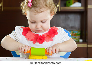 Cute little girl rolling clay dough with rolling pin
