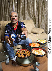 Man with remote control. - Portrait of a Middle-aged...