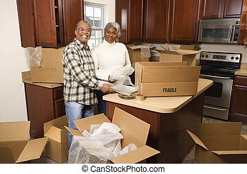 Couple unpacking boxes - Portrait of middle-aged...