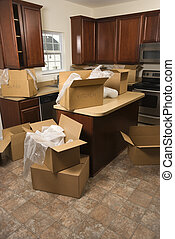 Moving boxes in kitchen. - Cardboard moving boxes with...