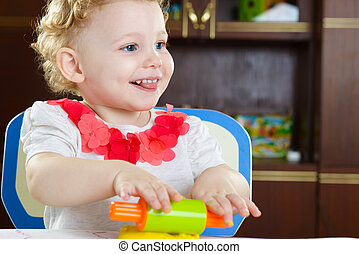 Cute smiling girl rolling plastiline dough at home