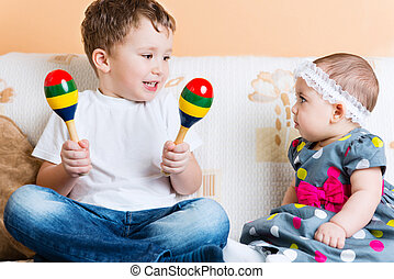 Cute little sister and her brother sitting with maracas on...
