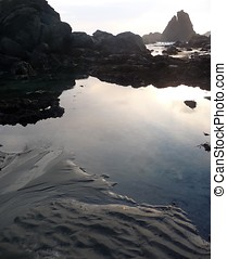 Tidepools reflect the sunset on a rocky coastal shorel 542A