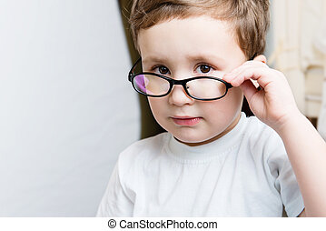 Portrait of serious kid in glasses