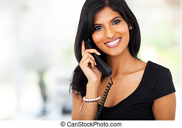 gorgeous young businesswoman answering telephone in office