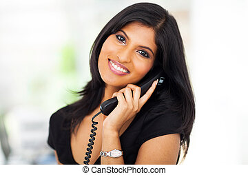 beautiful career woman talking on telephone in office