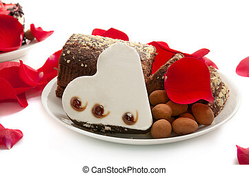 Heart shaped brownie with cake on the dish with rose petals