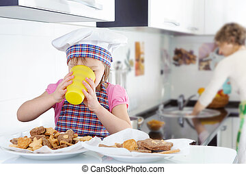 Little cute girl drinking milk in kitchen
