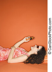 Woman with cellphone - Young Caucasian woman lying on floor...