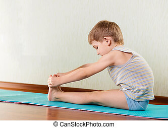 Little boy exercising and stretching in gym - Concentrated...