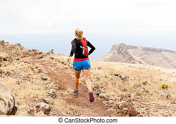 Young woman trail running in mountains - Young woman running...