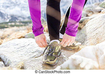 Female runner tying sports shoe in mountains on trail -...
