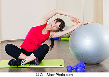 Young woman fitness workout in gym with fitball - Pretty...