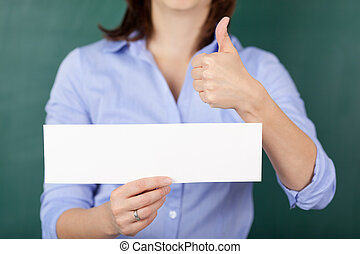 Teacher Holding Blank Paper While Gesturing Thumbs Up -...