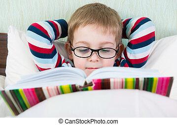 Little cute boy reading book in bed - Little cute boy in...