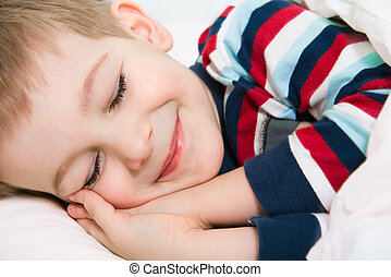 Little cute boy sleeping in bed smiling in dreams