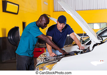 african man showing auto mechanic car problem - african man...