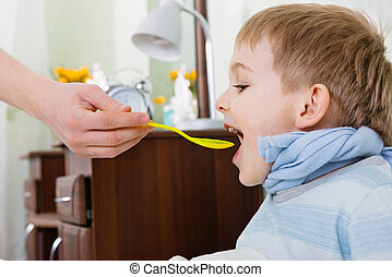 Sick boy taking medicine from spoon at home