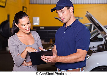 mechanic and customer - auto mechanic and female customer in...