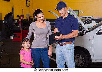 mother and daughter in garage with auto mechanic