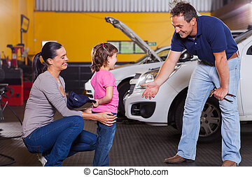 cute little girl hiding auto technician's hat
