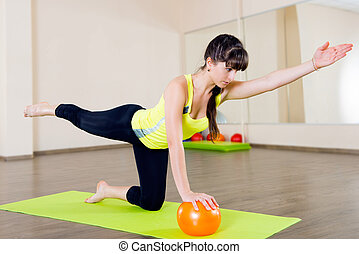 Pretty young girl fitness workout with little ball