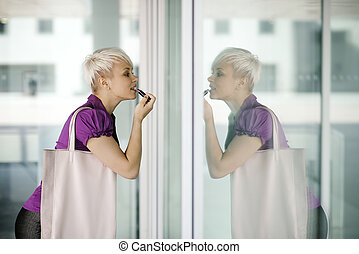 young business woman applying makeup in the street -...