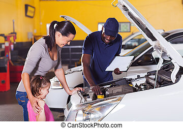 mother and little girl in car service center