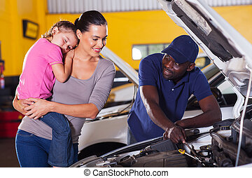 young mother taking her car for repair in garage with...