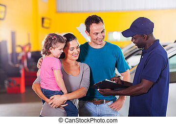friendly auto mechanic talking to young family in garage