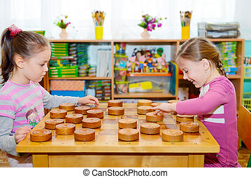 Two little girls playing in checkers in kindergarten