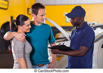 auto mechanic talking to young couple in repair shop