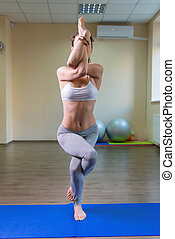 Young woman standing in yoga asana