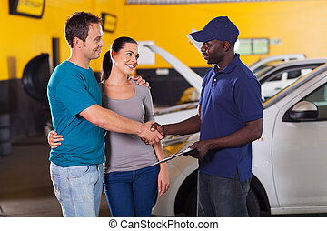 auto technician handshaking with couple - african auto...
