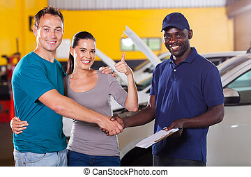 young couple giving thumb up to auto repair shop - happy...