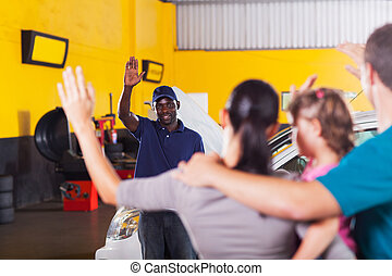 friendly auto repair shop worker waving good bye to customer...